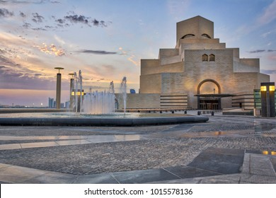 Doha,Qatar-April 28,2013 :Museum of Islamic Art , Doha,Qatar in daylight exterior view with fountain in foreground and clouds in the sky in the background