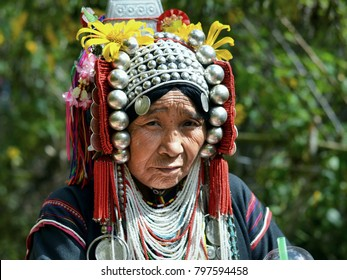 DOI HUA MAE KHAM, NORTHERN THAILAND - NOV 14, 2015: Old Akha woman with traditional silver head dress poses for the camera during the Bua Tong Festival in the Golden Triangle, on Nov 14, 2015.
