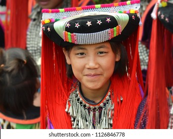 DOI HUA MAE KHAM, THAILAND - NOV 14, 2015: Pretty Flower Lisu preteen girl wears a multi-colored Lisu tunic with black and red circular Lisu headdress and poses for the camera, on Nov 14, 2015.