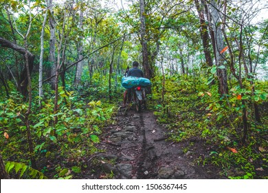 Doi Luang Tak, Tak Province, Thailand. AUGUST 31,2019: Porter driving a motorcycle in the rainy season at Doi Luang Tak, Tak Province,Thailand.