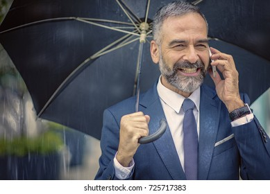 Doing business on a rainy day; senior mature business owner enjoying his time in rainy weather, talking to colleagues on his cell phone