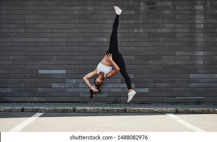 Doing crazy parkour and athletic stunts. Young sportive brunette with slim body shape against brick wall in the city at daytime.