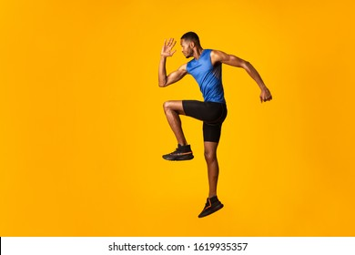 Doing Exercise. Full length portrait of muscular afro man with high knee, lifting leg and waving arm, copyspace
