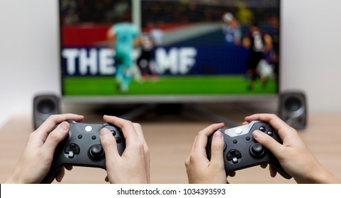 doing game with friend, two people hands and joystick game pads