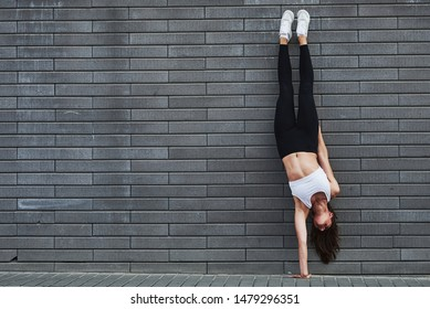 Doing handstand. Young sportive brunette with slim body shape against brick wall in the city at daytime.