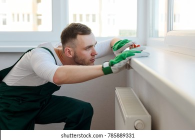 Doing home repair by yourself. Concetrated man looking at the level tool to inspect if the sill installed right. Repairman service concept.