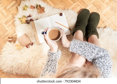 Doing hygge lifestyle at home with cup of coffee and warm socks