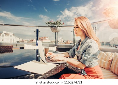 Doing job. Side view of attractive lady working on notebook computer. She is sitting at the table with cellphone, cup of coffee and papers