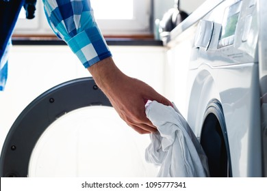 Doing the laundry. Man does the washing in washing machine. Cleaning clothes. Unusual role of a man in role of a woman. Man cares about the house. Father puts clothes in washing machine.