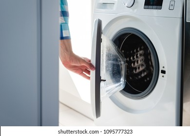 Doing the laundry. Opening the flap from the washing machine. Man does the washing in washing machine. Cleaning clothes. Unusual role of a man in role of a woman.