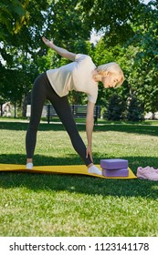 Doing morning fitness, yoga, pilates in the summer park. A slim blonde standing on the exercise mat with yoga bricks in front of her, bending over the leg,  stretching while trying to touch her toes.