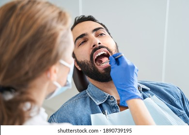 Doing professionally. Portrait view of the multiracial man sitting at the stomatology armchair while dentist examining his mouth with the mirror. Smiling man is having her teeth examined by dentist in