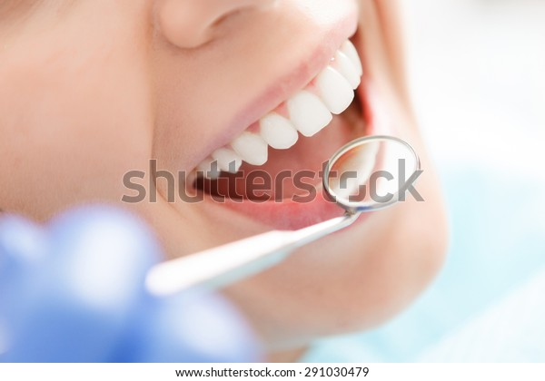 Doing professionally. Smiling pretty woman is having her teeth examined by dentist in clinic.