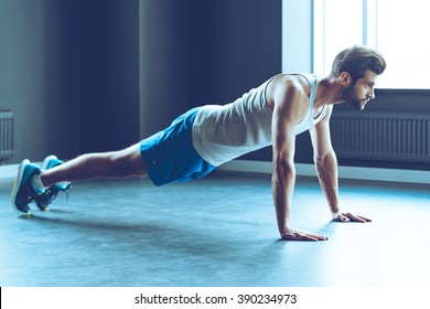 Doing push-up. Full length of young handsome man in sportswear doing push-up at gym