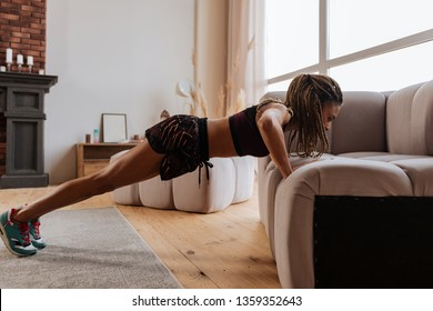 Doing pushups. Active fit woman wearing shorts and top doing pushups near sofa at home