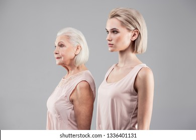 Doing same action. Tidy good-looking women displaying their height and age differences while standing close