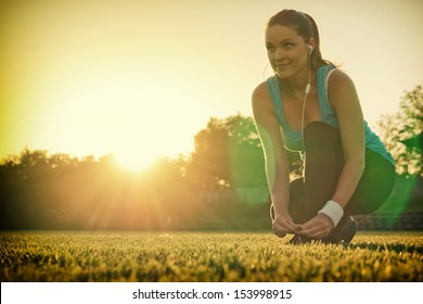 Doing Sport in the sunset / Young woman preparing to run in a playground, sunset in the background