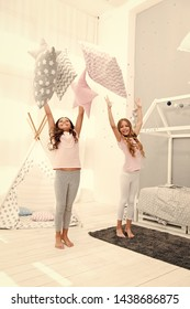 Doing whatever they want. Sleepover party ideas. Sisters play pillows bedroom party. Pillow fight pajama party. Girls happy best friends siblings in cute stylish pajamas with pillows sleepover party.