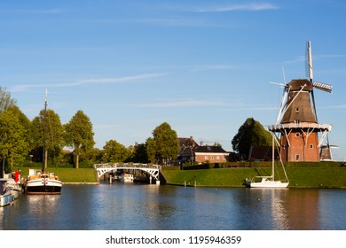 Dokkum, Friesland, The Netherlands - August 17, 2018; Boats on canal and windmill on fortifications of historic town Dokkum, Friesland, The Netherlands