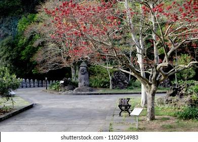 Dol Hareubang rock statue in garden park at Cheonjiyeon waterfall, Jeju Island, South Korea.