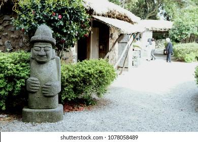 Dol hareubang rock statue at traditional  Seongeup Folk Village in Jeju Island, South Korea.
