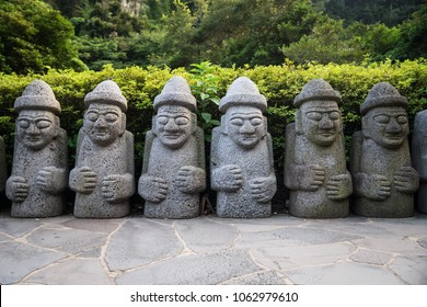 Dol Hareubang statues in a row with hats and hands on belly in green forest, Seogwipo, Jeju Island, South Korea