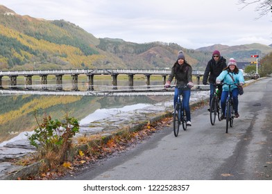 Dolgellau, Wales, UK - October 30th, 2018: Three cyclists on the disused railway track on the edge of the spectacular Mawddach estuary which links Dolgellau and Barmouth.