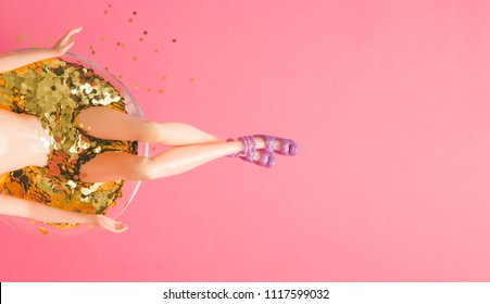 Doll bathing in martini glass full of gold glitter on pink background. Creative minimal beauty summer concept. Top view.