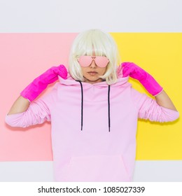 Doll Blonde Girl Model with beauty face in Fashion accessory sunglasses, gloves,  hoodie and shorts. Club DJ Party Fun. Mood and vibes. Minimal unicorn style. Pink and yellow neon colors. 90s or 80s