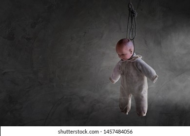 Doll figure hanging by the neck in the dark background.Suicide awareness concept.Baby kill concept.Child abuse concepts.The doll was hanged in a dark background.Horror hanged doll.