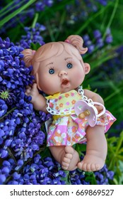 Doll with the  garden flowers on the background. l