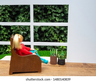 Doll girl with blonde hair and pony tail sitting in a big old chair looking out the window into the garden. Wooden floor and white wall with copy space. Dollhouse furniture and fake plants.