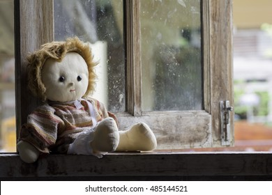 Doll girl sitting by the window alone .