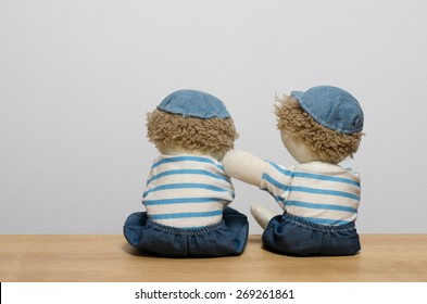A doll with a hand on the shoulder of another doll