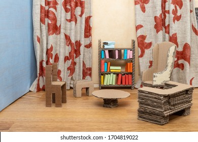Doll house cardboard furniture. With a sofa, chairs, table and bookcase. On a hardwood floor. Curtains and a blue wall.