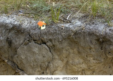 Doll house on the background of grass near a sandy cliff