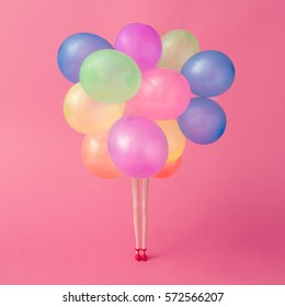Doll legs with colorfull balloons on pastel pink background. Minimal party concept.