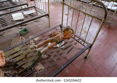 Doll on metal grid of bed in abandoned kindergarten in destroyed village Kopachi (10-km Chernobyl NPP alienation zone), Ukraine
