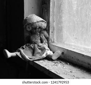 Doll on windowsill in abandoned kindergarten in destroyed village of Kopachi, Chernobyl NPP Exclusion Zone, Ukraine. Black and white image