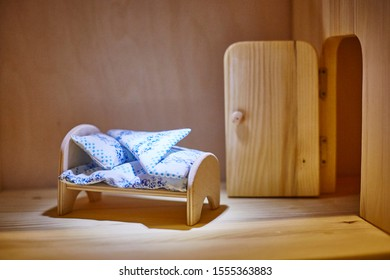 Doll plywood bed with blankets and pillows in the dollhouse. Miniature.