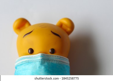 A doll wearing COVID19 mask and maintaining safety , background with light color