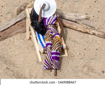 Doll woman on a blue and white wooden deck chair in the sand. Holding a white sun hat. Wearing a crop top and pants made from cotton fabric with an African print. Driftwood in the sand.