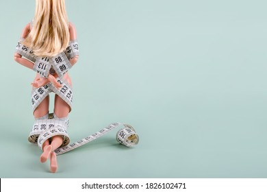 Doll wrapped in measuring tape. Tied up fashion doll, weight loss concept. Fasting, weightloss and slimming. Diet, anorexia, eating disorder, overeating control, female fight for perfect fit body.