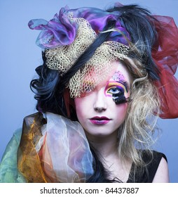 Doll. Young pretty lady with creative make-up and in exotic hat.