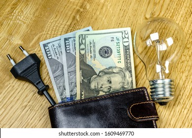 Dollar banknotes and an electric plug in a wallet - electricity cost concept
