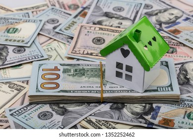 dollar banknotes and a model house on a construction plan for house building; concept of buying a house. Real Estate dollar house background.