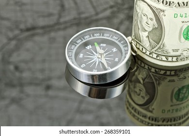 dollar bill and compass are on the surface which reflects map