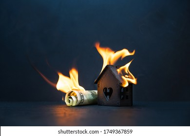 A dollar bill and a model of a black house are on fire on a dark background. Collapse, crisis, sale or destruction of a home.