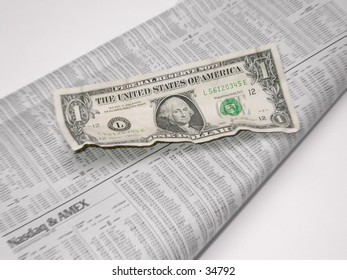 A dollar bill and the stocks section of the newspaper.