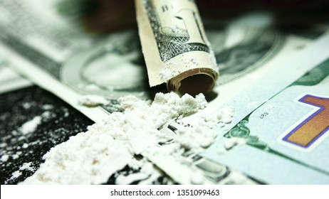 Dollar bill, white powder (like cocaine). Close up, macro. One hundred dollars and a lot of cocaine are scattered on the table. Twisted Dollar bill, through which sniffs cocaine. Illegal drugs